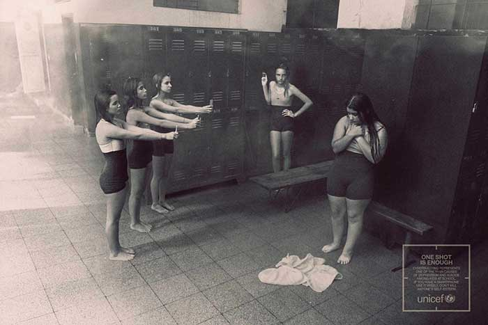 Anuncio de Unicef donde se ven a 4 niñas riéndose de otra niña gorda en un vestuario y sacándole fotos con el móvil. Fotografía en blanco y negro.