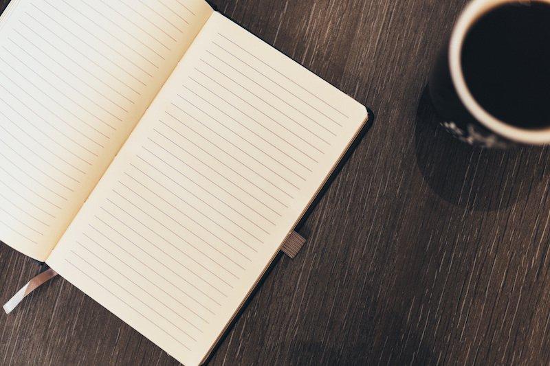 Libreta a rallas abierta con café al lado. Las mejores frases de marketing online