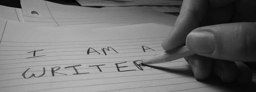Mano escribiendo I am a writer en lápiz en blanco y negro.